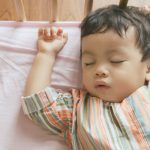little-boy-toddler-adorably-sleeping-in-his-baby-cot-while-wearing-picture-id1222732527