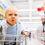 young-mother-with-her-little-baby-boy-at-the-supermarket-picture-id875222634