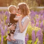 happy-mother-and-son-in-the-blooming-lupine-field-picture-id841467472