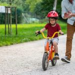 little-boy-learning-to-ride-a-bicycle-with-support-from-his-father-picture-id1213868636